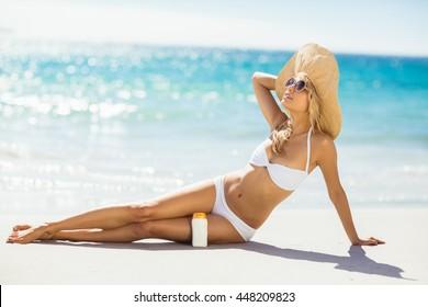Attractive woman posing with sun cream on beach