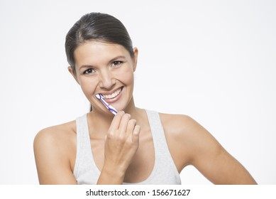 Attractive woman practicing dental hygiene brushing her teeth with a toothbrush and toothpaste to prevent tooth decay or caries , isolated on white