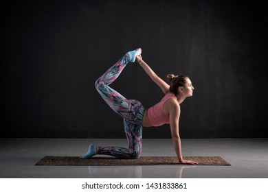 Attractive woman practicing yoga, doing tiger exercise, or Bird dog pose, working out in studio on black background