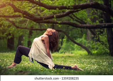 attractive woman practicing yoga in nature
