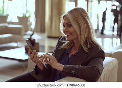 Attractive woman pratcising social distancing in a hotel lobby while completing a contactless online hotel room check-in on her smartphone