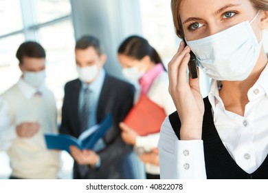 Attractive woman in protective mask calling somebody in working environment