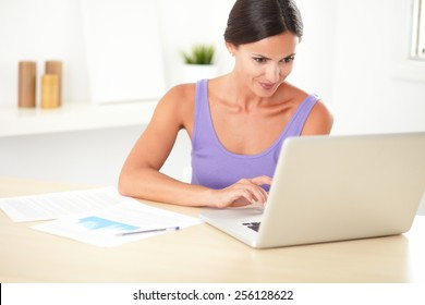 Attractive woman in purple t-shirt learning on her computer at her home