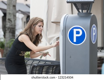 Attractive woman putting money in a parking meter