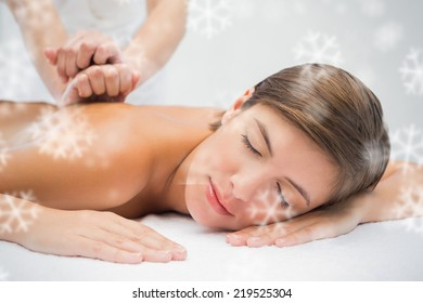 Attractive woman receiving back massage at spa center against snowflakes