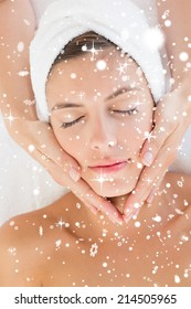 Attractive woman receiving facial massage at spa center against snow falling