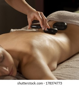 Attractive woman receiving a relaxing hot stone massage on her back.
