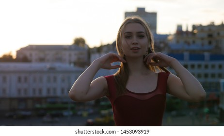 Attractive woman in red balet tiptoe posing for the photo on the outdoor