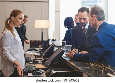 Attractive woman registering on arrival in hotel