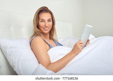 Attractive woman relaxing in comfortable neutral white bed with a tablet computer in her hands and a friendly smile