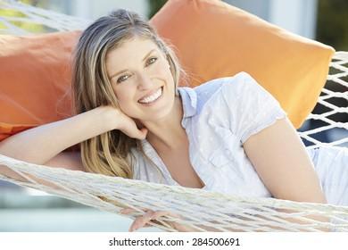Attractive Woman Relaxing In Garden Hammock