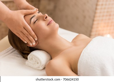attractive woman relaxing and having head massage in massage salon