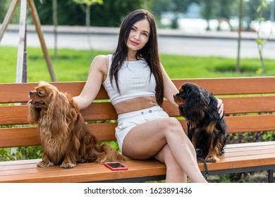 Attractive woman relaxing with her two adorable dogs. Two cavalier king charles spaniel dogs.