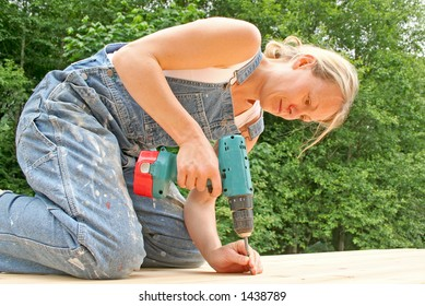 An attractive woman renovates the deck of her new home.