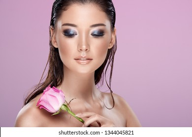 Attractive woman with rose, wearing nude make up with long lashes and perfect skin, pink background.