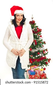 Attractive woman with Santa hat standing near Christmas tree with presents isolated on white background