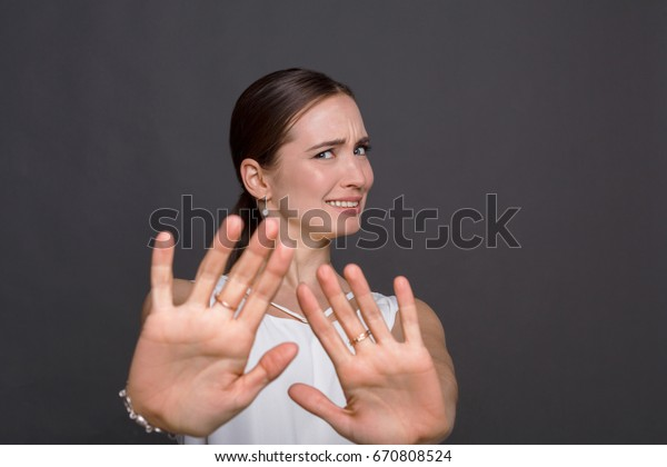 Attractive woman saying thanks but no. Beautiful girl denying proposal, making stop gesture with her hands, looking at camera