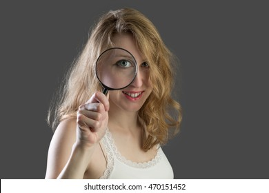 Attractive woman scoping through a magnifying glass