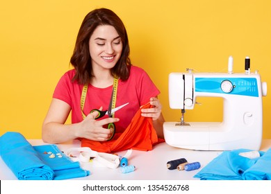 Attractive woman seamstress tailor sitting attable with sewing machine on yellow background in studio. Young dressmaker cuts piese of cloth for new dress. Sewer wears red t shirt with happy expression