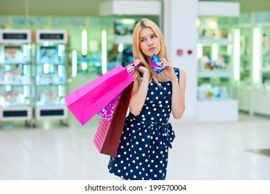 attractive woman with shopping bags holding credit card