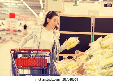 Attractive woman shopping in supermarket. Closeup portrait beautiful young woman picking up, choosing fruits in grocery store. Healthy life style dieting daily errands concept