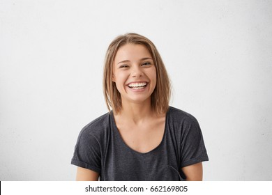 Attractive woman with short fair hair being very glad smiling with broad smile showing her perfect teeth having fun indoors. Joyful excited cheery femlae rejoicing after being proposed to marry