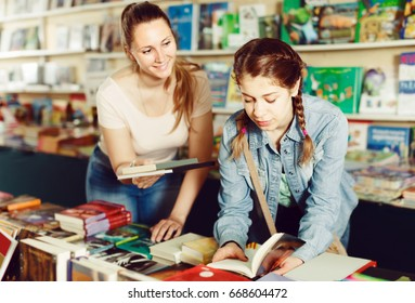 attractive woman showing open book to girl in school age in book boutique