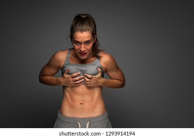 Attractive woman showing six pack abdominal muscles. Female trained figure. Active lifestyle, sports and Fitness. Strong and Beautiful body. Place for Advertising