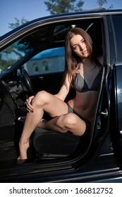 Attractive woman sitting in a car with its door open wearing a two piece swim suit.