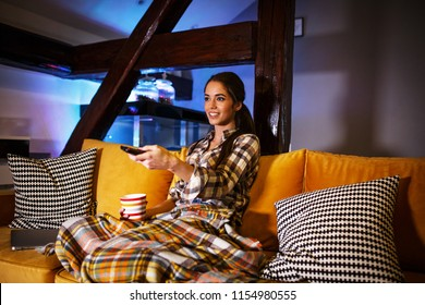 Attractive woman sitting at home on pleasant evening and watching a movie.
