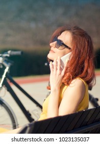 Attractive woman sitting on bench with phone in her hands