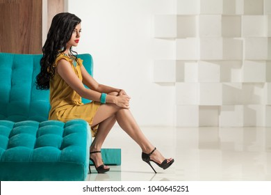 Attractive Woman sitting on Comfortable Sofa on White Background