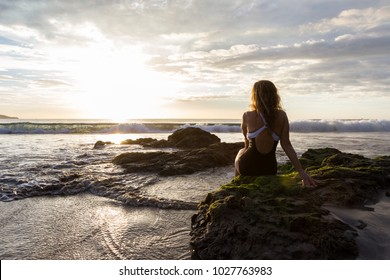 attractive woman sitting on the rocks enjoying a beautiful sunset in Playa Flamingo, Costa Rica