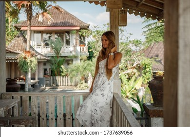 Attractive woman sitting on veranda of wooden house, relaxed summery atmosphere. Vacation on Bali, Ubud
