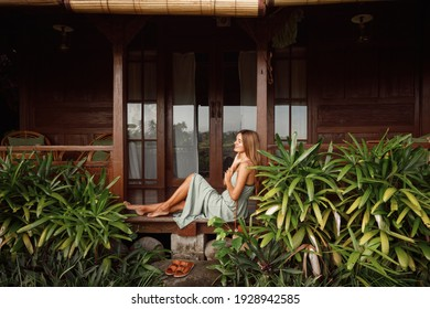 Attractive woman sitting on veranda of wooden house, relaxed summery atmosphere. Vacation on Bali, Ubud. Tropical view on background, palm tree and rice terraces