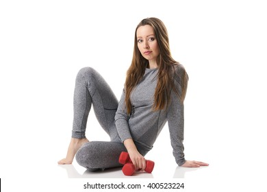 Attractive woman in sitting position two red dumbbells keeping in one hand in gray thermal underwear on white background.