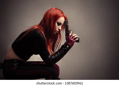 attractive woman sitting thinking with gun