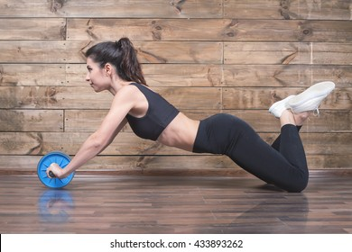 Attractive woman with slim stomach do abdominal exercises with wheel. Workout exercise at home to lose weight
