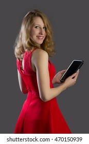 An attractive woman, smiling and holding a tablet