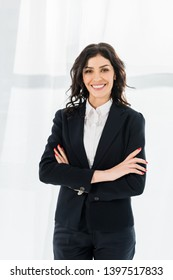 attractive woman smiling while standing with crossed arms