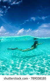 Attractive woman snorkeling in tropical waters and enjoying her beach vacation