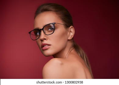 Attractive woman in square eyeglasses looking at camera on red background. Portrait of young beautiful blonde girl.Black frame spectacles.Vision correction,optical shop,glasses store,eyewear concept.