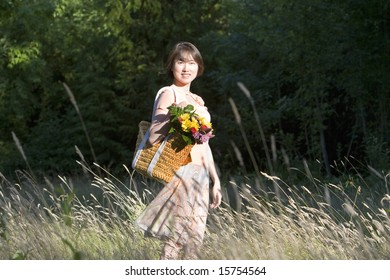 Attractive woman stands in a field while holding a basket containing a bouquet of flowers. She is standing to the side, smiling.  Vertically framed photo.