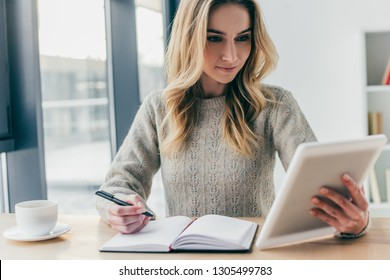 attractive woman studing with digital tablet while holding pen near notebook