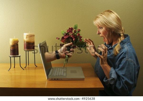 Attractive woman stunned from the flower handed to her coming through her laptop screen.