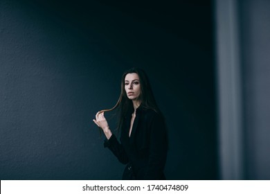 Attractive woman in stylish coat posing against city wall
