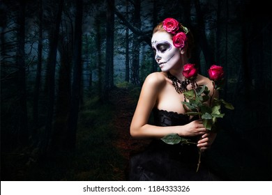 attractive woman with sugar skull make-up in front of creepy forest scene