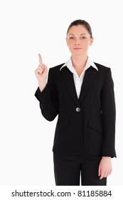 Attractive woman in suit pointing at a copy space while standing against a white background
