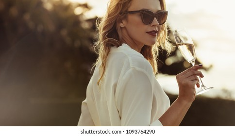 Attractive woman in sunglasses drinking wine outdoors. Beautiful female having a glass of wine looking backwards.