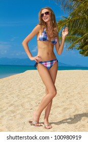 Attractive woman with sunglasses on sandy tripical beach
